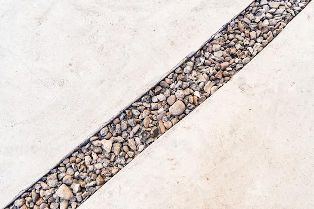 Cement achtergrond doorkruist door een diagonale lijn van kiezelstenen steen Gratis Foto