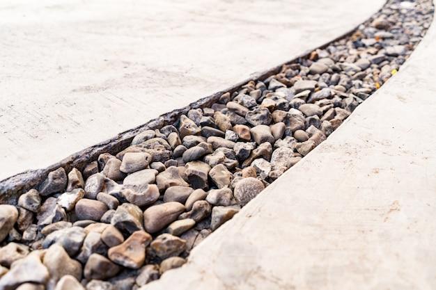 Cement doorkruist door een diagonale lijn van kiezelstenen steen Gratis Foto