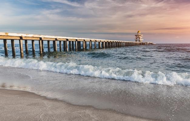 Cement loopbrug in het strand naar de zee. Premium Foto