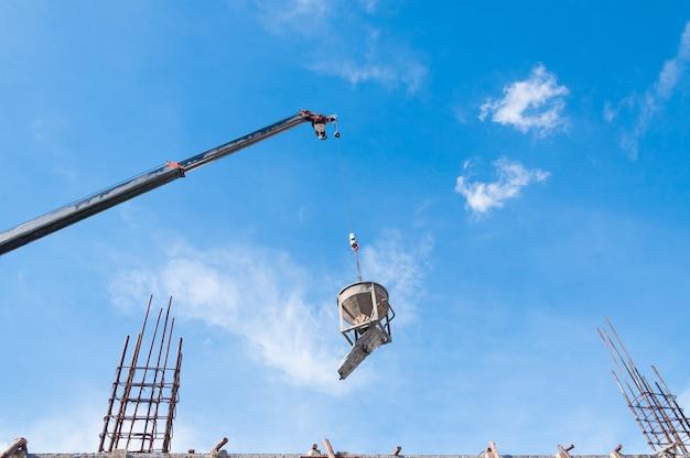 Cement of betonnen emmer opknoping op draad op bouwplaats met blauwe lucht Premium Foto