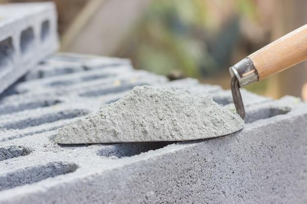 Cementpoeder met een troffel op de baksteen voor bouwwerkzaamheden Premium Foto