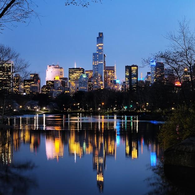 Central park in schemer en gebouwenbezinning in de stad van manhattan van de binnenstad in new york Premium Foto