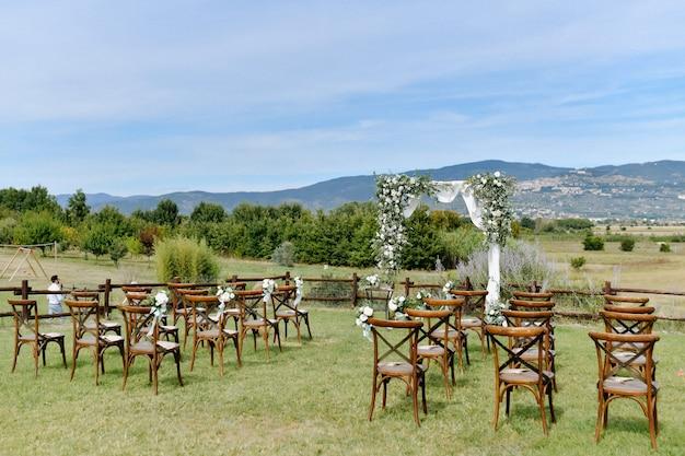 Ceremoniële huwelijksboog en chiavari-stoelen voor gasten in openlucht Gratis Foto