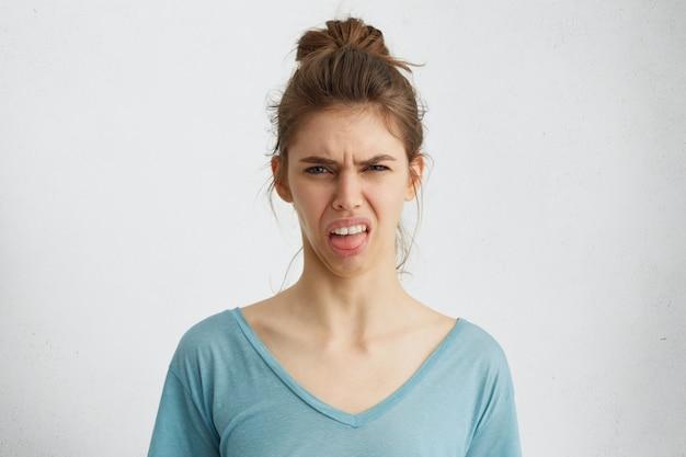 Chagrijnige vrouw toont haar walging terwijl fronsen gezicht met ontevredenheid met haar tong. Gratis Foto