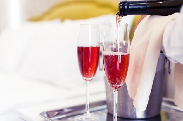 Champagne-emmer dichtbij bed in een hotelkamer Premium Foto