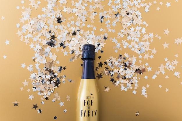 Champagne-fles met lovertjes op lijst Gratis Foto