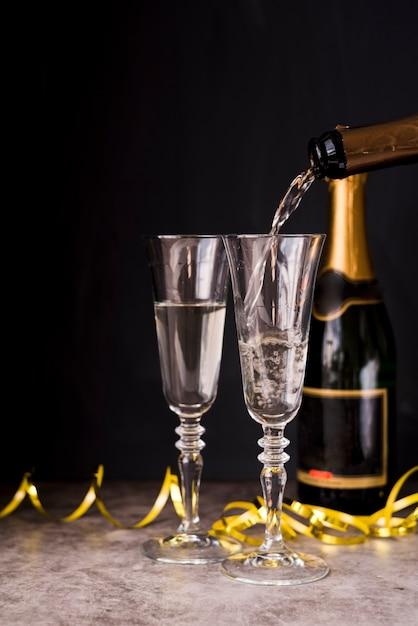Champagne gieten in het glas met streamers op feestje Gratis Foto