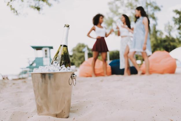 Champagne ice bucket friends opknoping op het strand Premium Foto