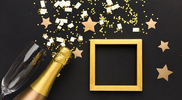 Champagnefles en glas naast frame Gratis Foto