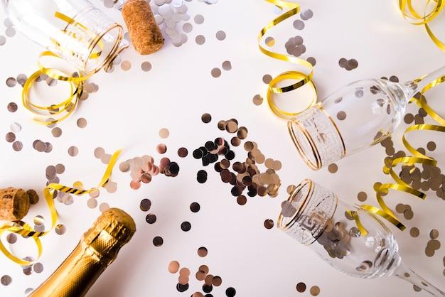 Champagnefles met lege glazen; confetti en streamers op witte achtergrond Gratis Foto