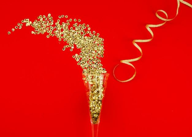 Champagneglas en gouden glitter Gratis Foto