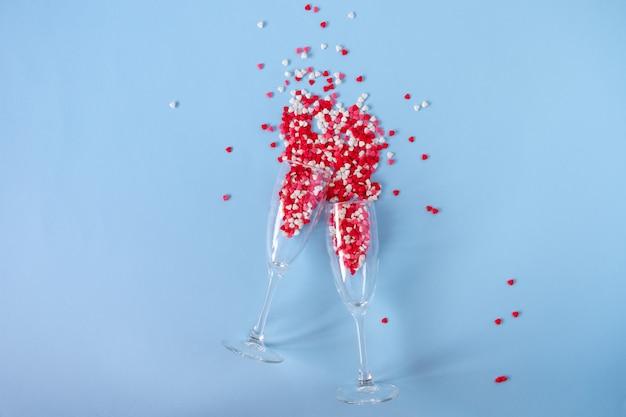 Champagneglazen met scheutje rode hartvormige kandijsuiker. valentijnsdag, verjaardag of bruiloft concept. plat liggen. bovenaanzicht. kopieer ruimte. Premium Foto