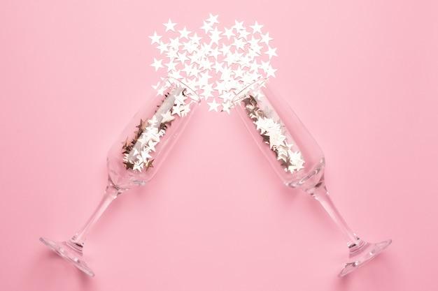 Champagneglazen met zilveren sterrenconfettien op roze kleurendocument minimale stijl als achtergrond Premium Foto