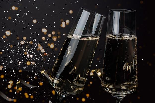 Champagneglazen op een donkere muur met sneeuw en lichten. oudejaarsavond, kerstmis Premium Foto