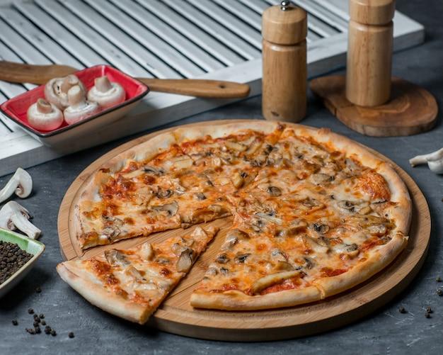 Champignonpizza, een plak afgesneden op een houten bord Gratis Foto