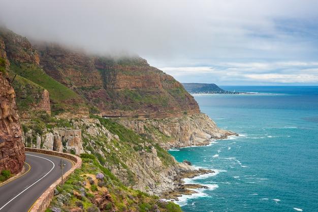 Chapman's peak drive, kaapstad, zuid-afrika. ruwe kustlijn in wintertijd, bewolkte en dramatische hemel, golvende atlantische oceaan. Premium Foto