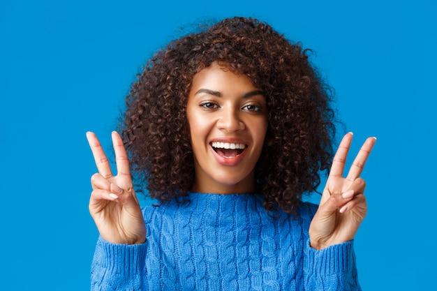Charismatisch opgewonden en blij, lachende vrolijke afro-amerikaanse vrouw die positieve vibes verzendt, vredesgebaar toont en grijnst, genietend van wintervakantie, nieuwjaarsfeest, zeg kaas Premium Foto