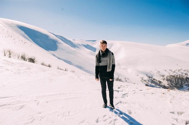 Charismatische knappe jonge man die tegen een achtergrond van besneeuwde bergen stelt Premium Foto