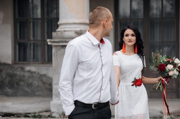Charmant en stijlvol bruidspaar vormt voor een gebouw van een oud kasteel Gratis Foto