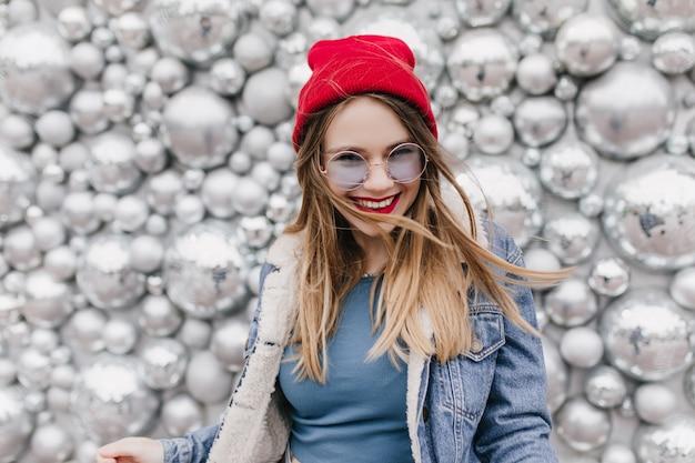 Charmant europees meisje in schattige rode hoed poseren met een gelukkige glimlach. foto van mooie blonde vrouw in spijkerjasje dat zich naast de ballen van de fonkelingsdisco bevindt. Gratis Foto