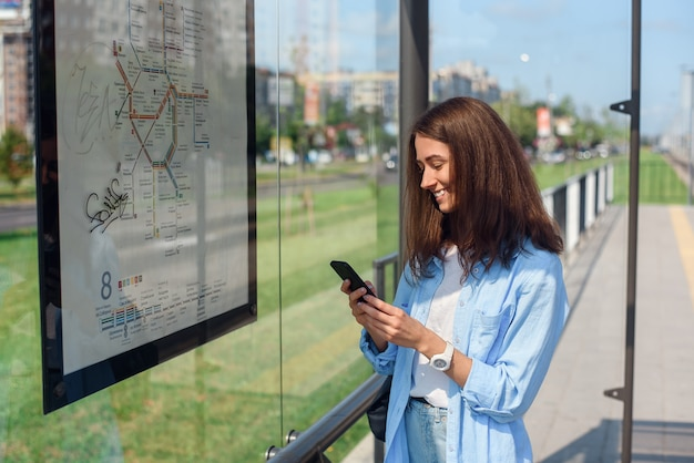 Charmant jong meisje volgt de bus via een mobiele app terwijl ze 's ochtends bij een halte van het openbaar vervoer staat. Premium Foto