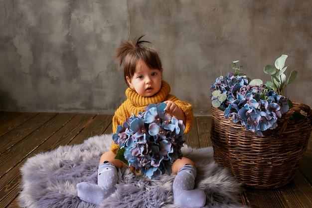 Charmant klein baby-meisje in oranje trui verkent blauwe hortensia zittend op warme deken Gratis Foto