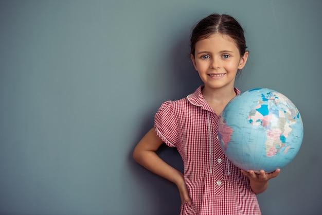 Charmant klein meisje in schattige jurk houdt een wereldbol. Premium Foto