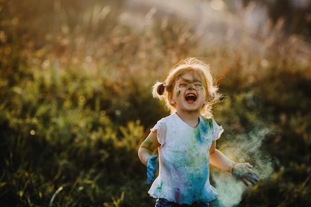 Charmant klein meisje met wit shirt bedekt met verschillende verven Gratis Foto