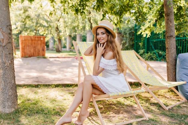 Charmant meisje in vintage schipper na te denken over iets aangenaams zittend in gele chaise-longue. knappe glimlachende dame in witte jurk poseren in tuin in weekend. Gratis Foto