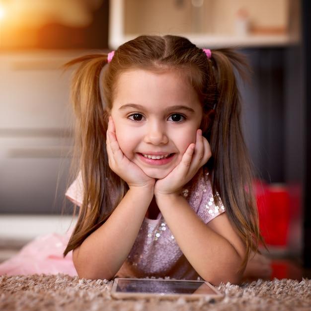 Charmant meisje met mooi kapsel camera kijken cartoons kijken Premium Foto