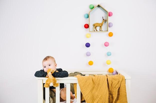 Charmante baby in wieg kauwende stuk speelgoed Premium Foto