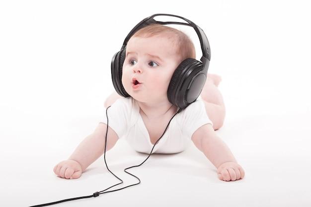 Charmante baby op een wit met koptelefoon luisteren naar muziek Premium Foto