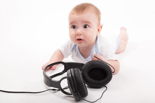 Charmante baby op een witte achtergrond met koptelefoon luisteren naar Premium Foto