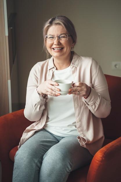 Charmante blanke senior vrouw met bril een thee drinken en zittend op de bank Premium Foto