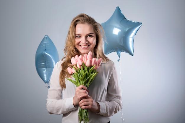 Charmante blije vrouw met boeket bloemen en ballonnen Gratis Foto