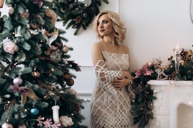 Charmante blonde vrouw in witte jurk vormt in een kamer met grote kerstboom Gratis Foto