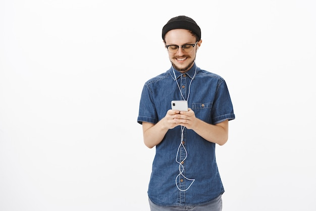Charmante en vrolijke knappe volwassen man in muts en bril met baard messaging tijdens reizen in de metro smartphone luisteren muziek in oordopjes te houden, tevreden met schattige romantische noot Gratis Foto
