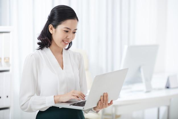 Charmante etnische zakenvrouw met behulp van laptop Gratis Foto