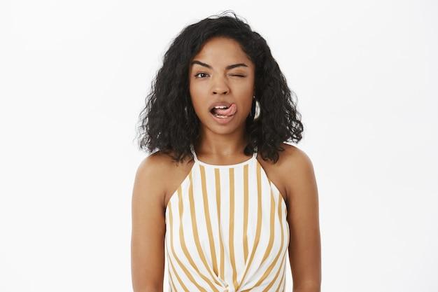 Charmante, gedurfde en sensuele flirterige vrouw met een donkere huidskleur in een gestreepte gele top met een knipoog en een tong uitsteekt Gratis Foto
