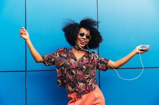Charmante geweldige afro-amerikaanse jonge vrouw in zonnebril, dansen Gratis Foto