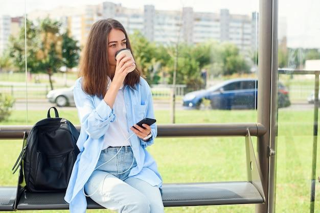 Charmante hipster meisje bus of tram wachten op het openbaar vervoer station in de ochtend met een kopje koffie Premium Foto