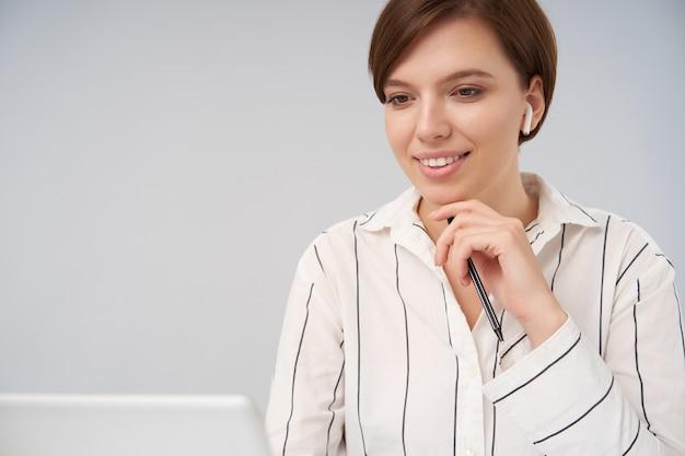 Charmante jonge bruinharige dame met natuurlijke make-up zachtjes haar kin aan te raken met opgeheven hand en vooruit te kijken met een aangename glimlach, geïsoleerd op wit Gratis Foto