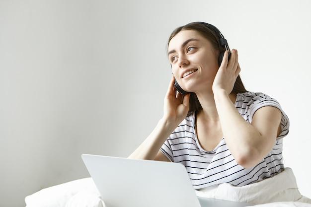 Charmante jonge donkerharige vrouw weekend ochtend doorbrengen in bed met laptop, genieten van nieuwe muzieknummers Gratis Foto