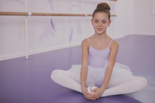Charmante jonge meisjesballerina die op dansschool uitoefenen Premium Foto