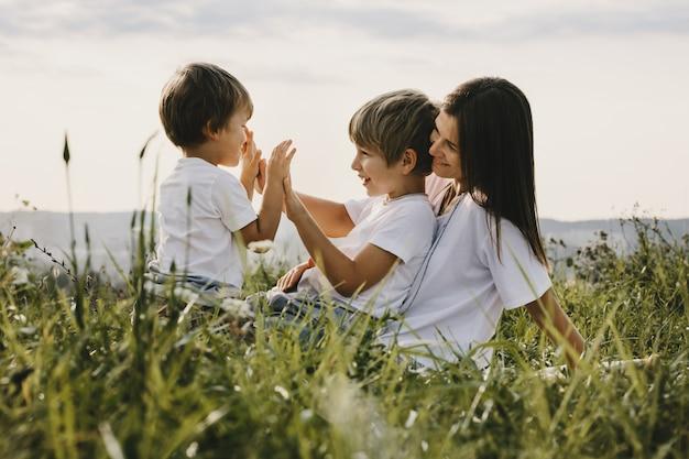 Charmante jonge moeder heeft plezier met haar kleine zonen Gratis Foto