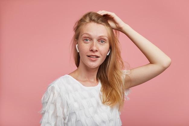 Charmante jonge verrast roodharige vrouw met groen-grijze ogen die haar haar vasthoudt met opgeheven hand en positief naar de camera kijkt, staande tegen een roze achtergrond Gratis Foto