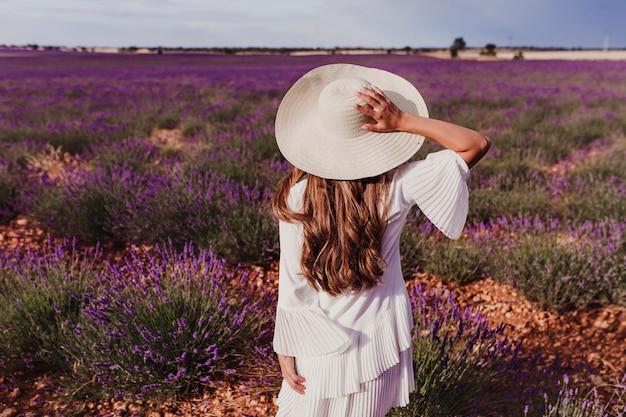Charmante jonge vrouw met een hoed en witte jurk in een paarse lavendel veld bij zonsondergang. levensstijl buitenshuis. achteraanzicht Premium Foto
