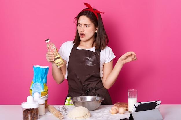 Charmante jongedame die bakkerij maakt in de keuken, veel ingrediënten en gebruiksvoorwerpen gebruikt om deeg te kneden, kijkt met verbazing op een fles olie, gebruikt een tablet om nieuwe recepten te maken. kopieer ruimte. Premium Foto