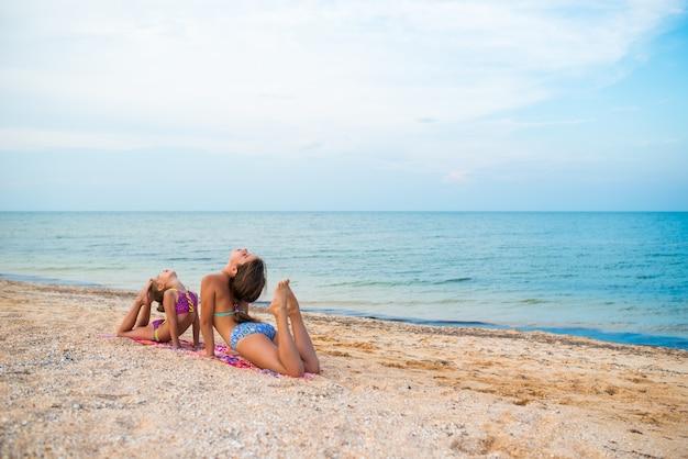 Charmante kleine meisjes doen gymnastiekoefeningen terwijl ze op een zonnige warme zomerdag ontspannen op het strand Premium Foto