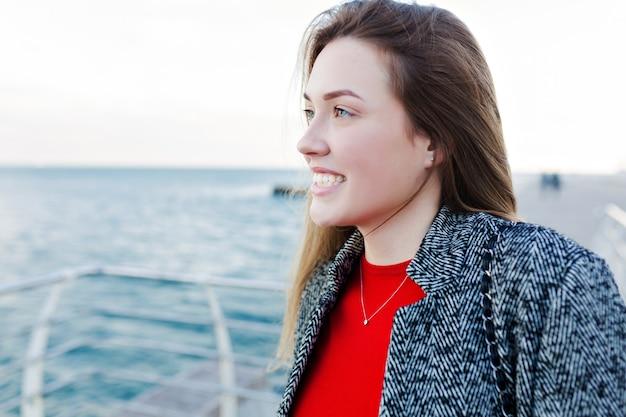 Charmante, lieftallige vrouw met lang lichtbruin haar in een grijze vacht om de zee en het mooie weer op de kade te bewonderen Gratis Foto
